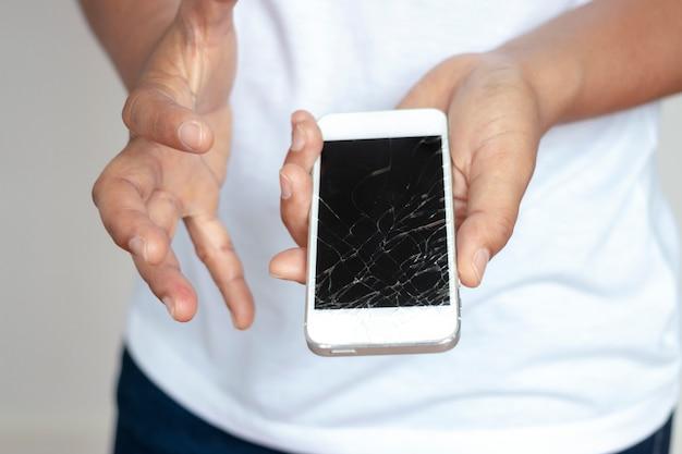 Donna che tiene il telefono che ha lasciato cadere lo schermo, rotto nella mano, molto triste. Foto Premium