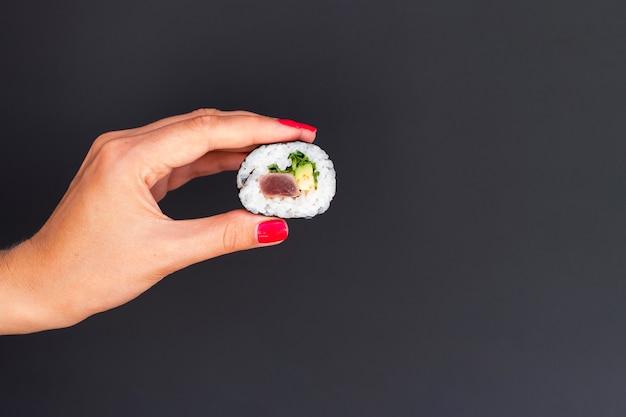 Donna che tiene in mano un pezzo di rotolo di sushi Foto Gratuite