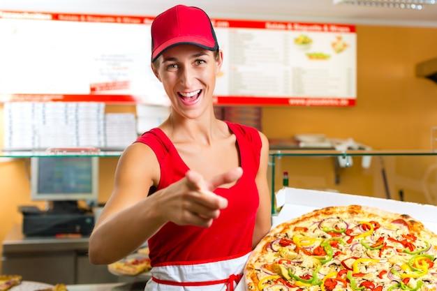 Donna che tiene in mano una pizza intera Foto Premium
