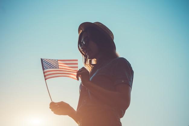 Donna che tiene la bandiera usa. celebrando l'independence day of america Foto Premium
