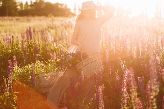 Donna che tiene la borsa di vimini in sue mani che porta il cappello della fedora sul tramonto nel campo del lupino Foto Gratuite