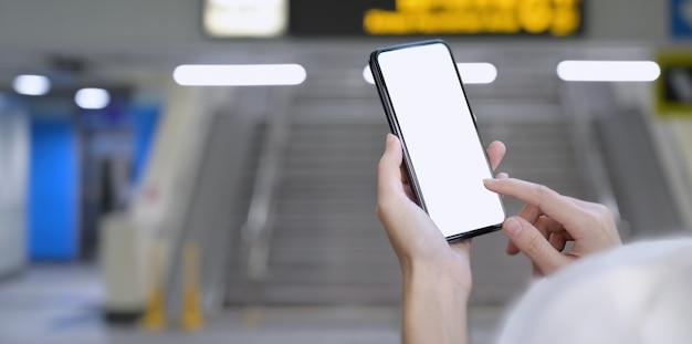 Donna che tiene lo smartphone dello schermo in bianco alla stazione ferroviaria Foto Premium