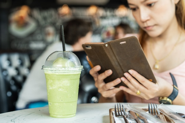 Donna che tiene smart phone mobile prendendo foto al frappe di tè verde Foto Premium