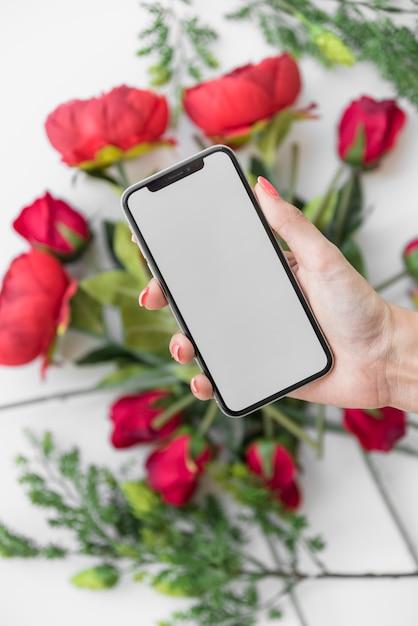Donna che tiene smartphone con schermo vuoto sopra rose Foto Gratuite