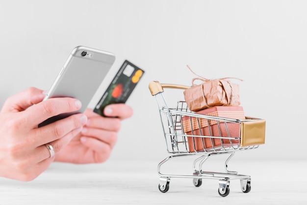 Donna che tiene smartphone e carta di credito Foto Gratuite