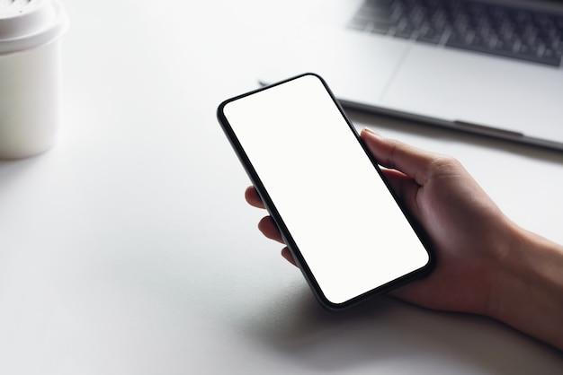 Donna che tiene smartphone mockup di schermo vuoto sul tavolo. Foto Premium