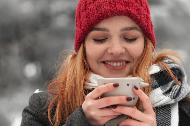 Donna che tiene tazza di tè e sorrisi Foto Gratuite