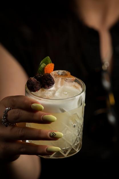 Donna che tiene un bicchiere di cocktail guarnito con lamponi secchi Foto Gratuite