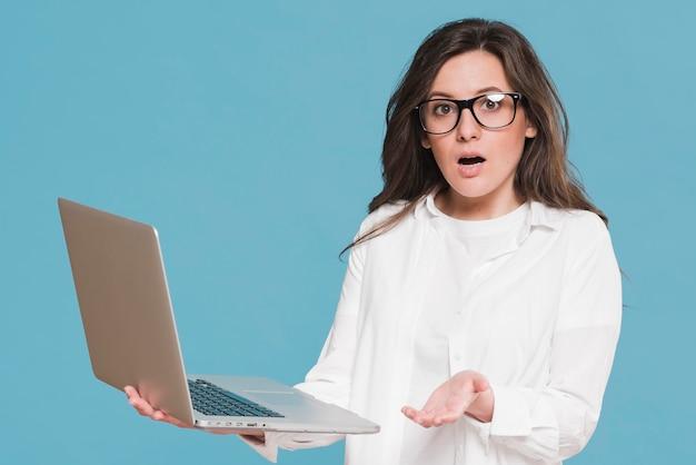 Donna che tiene un computer portatile e che è sorpresa Foto Gratuite