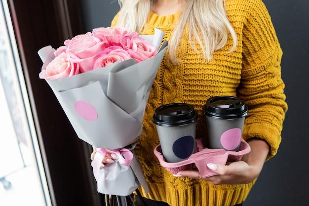 Donna che tiene un contenitore speciale per due tazze di caffè per andare e un mazzo di fiori rosa. Foto Premium