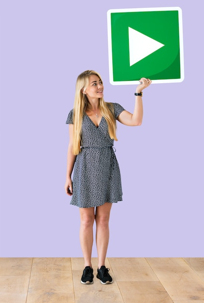 Donna che tiene un'icona del tasto di riproduzione in uno studio Foto Gratuite