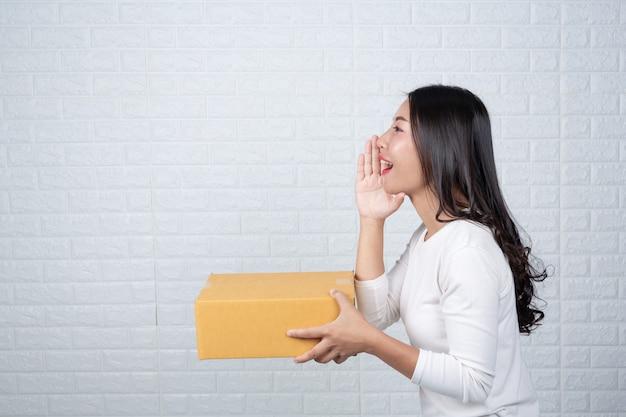 Donna che tiene una casella di posta marrone fatto gesti con la lingua dei segni. Foto Gratuite