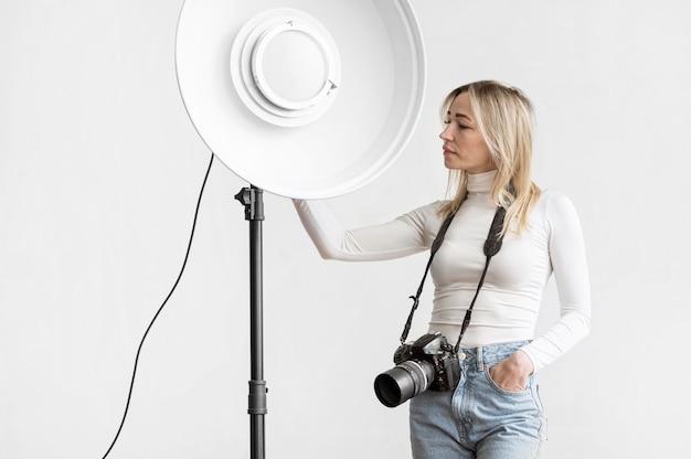 Donna che tiene una lampada dello studio Foto Gratuite
