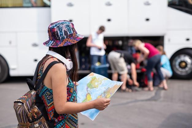 Donna che tiene una mappa presso la stazione ferroviaria concetto di turismo Foto Gratuite