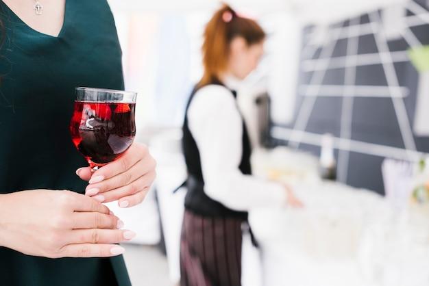 Donna che tiene vetro con alcool Foto Gratuite