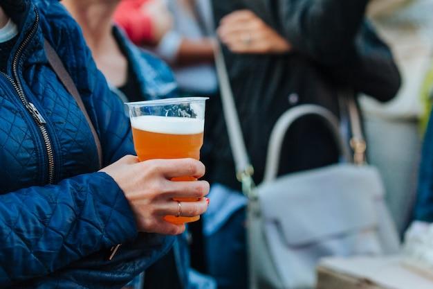 Donna che tiene vetro di plastica con birra al festival Foto Premium