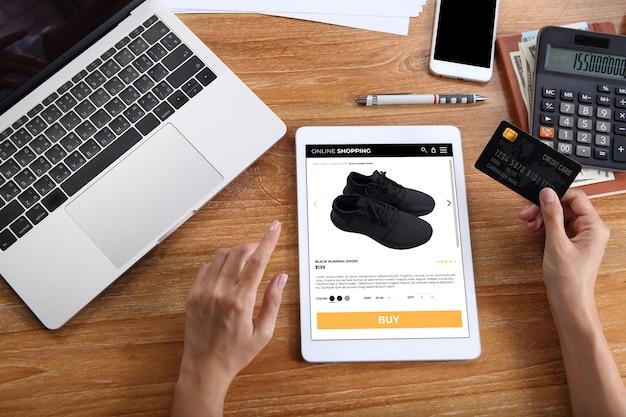 Donna che usando la carta di credito per comprare scarpe da corsa nere sul sito web di e-commerce tramite tablet con laptop, smartphone e cancelleria per ufficio sulla scrivania in legno Foto Premium