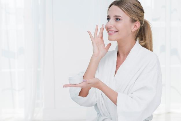 Donna che usando la crema di bellezza in una stazione termale Foto Gratuite