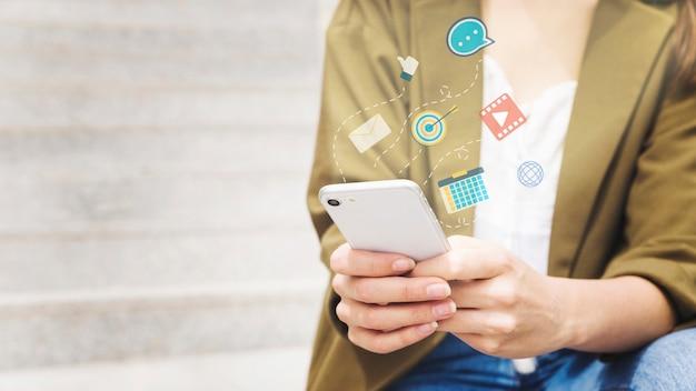 Donna che utilizza cellulare con diverse applicazioni Foto Gratuite