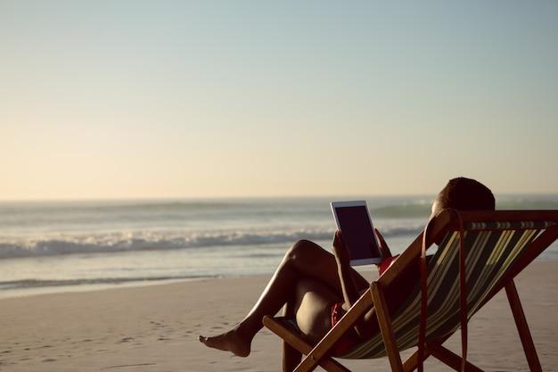 Donna che utilizza compressa digitale mentre rilassandosi in una sedia di spiaggia sulla spiaggia Foto Gratuite