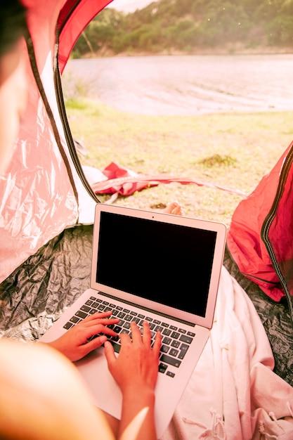 Donna che utilizza computer portatile in tenda Foto Gratuite