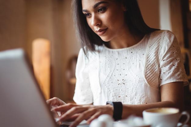 Donna che utilizza computer portatile nel café Foto Gratuite