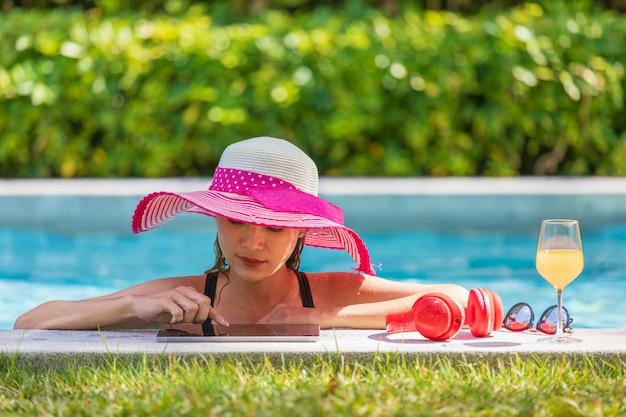 Donna che utilizza computer tablet in piscina Foto Premium