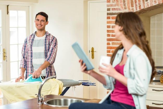 Donna che utilizza i vestiti rivestenti di ferro dell'uomo e della compressa in cucina Foto Premium