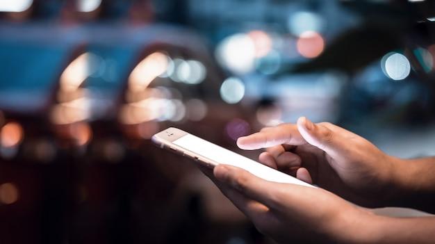 Donna che utilizza il suo telefono cellulare in strada, luce notturna sfondo, skyline della città notte lig Foto Premium