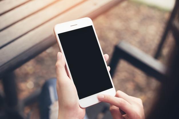 Donna che utilizza smartphone dello schermo in bianco. concetti per la tecnologia digitale nella vita di tutti i giorni. Foto Premium
