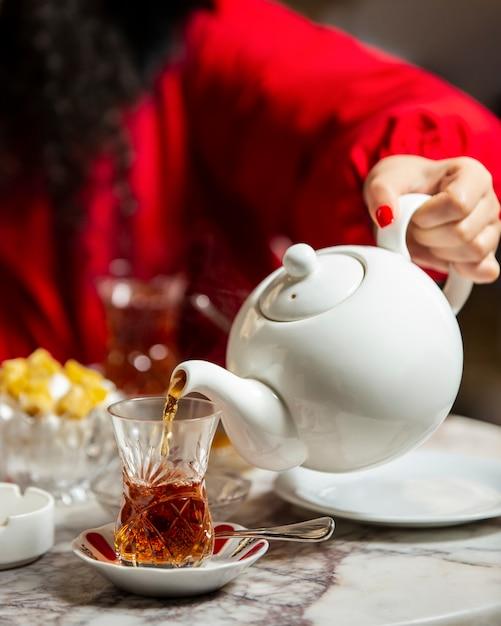 Donna che versa tè nero dalla teiera nel bicchiere armudu Foto Gratuite