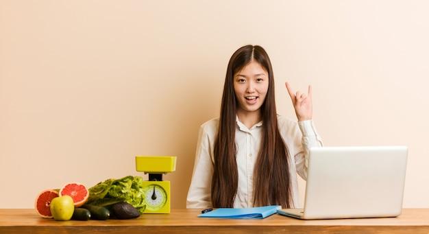 Donna cinese del giovane dietista che lavora con il suo computer portatile che mostra un gesto dei corni come concetto di rivoluzione. Foto Premium