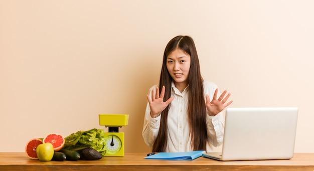 Donna cinese del giovane dietista che lavora con il suo computer portatile che rifiuta qualcuno che mostra un gesto di disgusto. Foto Premium