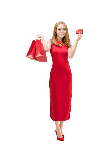Donna cinese del ritratto con il vestito dal cheongsam che tiene i sacchi di carta rossi e che mostra la carta di credito Foto Premium
