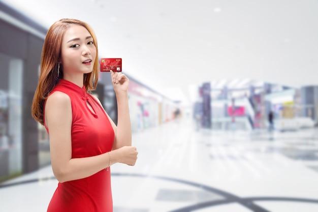 Donna cinese sorridente con la carta di credito della tenuta del vestito tradizionale Foto Premium