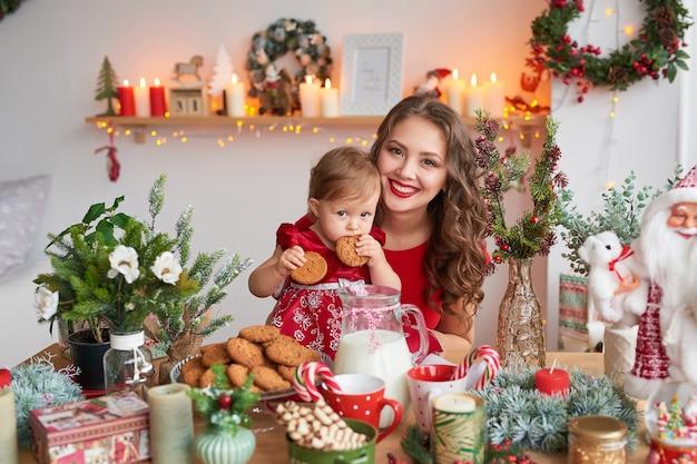 Donna con bambino in cucina decorato per natale. Foto Premium