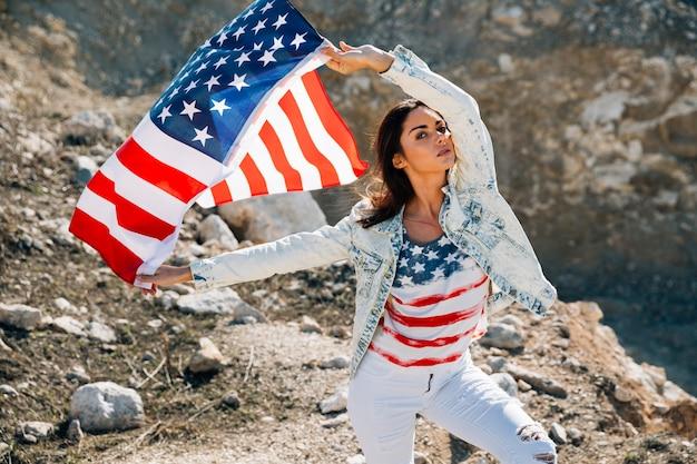 Donna con bandiera usa guardando la fotocamera Foto Gratuite