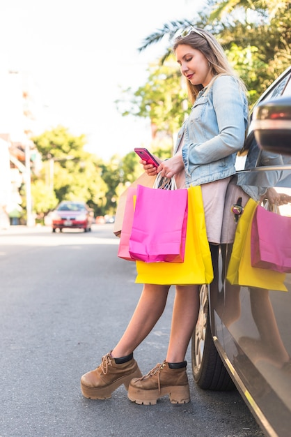 Donna con borse della spesa utilizzando smartphone in auto Foto Gratuite