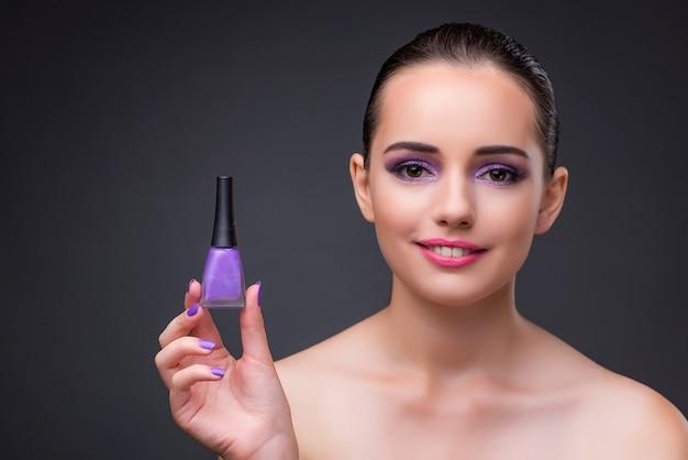 Donna con bottiglia di smalto per unghie Foto Premium