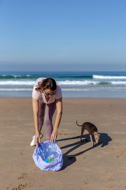 Donna con cane raccogliendo rifiuti e materie plastiche che puliscono la spiaggia Foto Premium