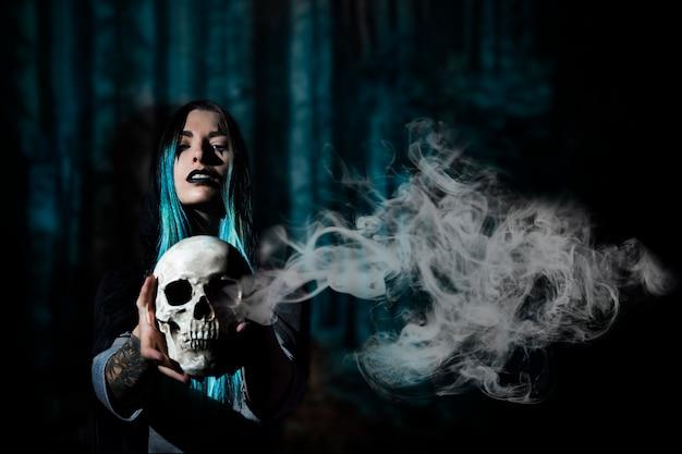 Donna con capelli blu che tengono un cranio con fumo Foto Gratuite