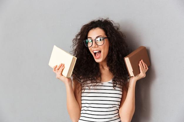 Donna con capelli ricci marroni che sono studente in università che posa con i libri interessanti in mani che prendono piacere nell'istruzione isolata sopra la parete grigia Foto Gratuite