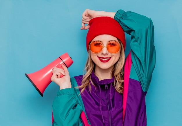 Donna con cappello rosso, occhiali da sole e vestito degli anni '90 con altoparlante Foto Premium