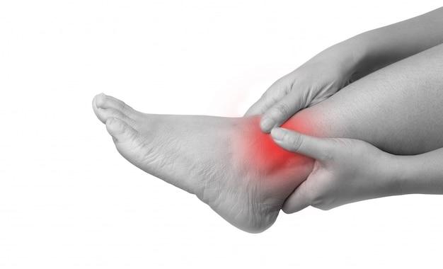 Donna con dolore alla caviglia con due mani che tengono la gamba e massaggiandola dolorosa Foto Premium