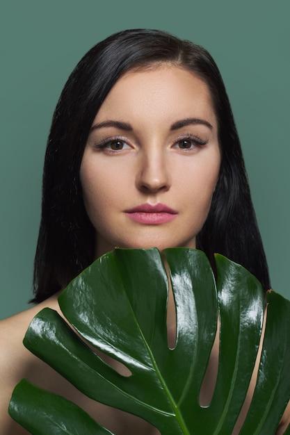 Donna con foglia verde, femmina con bellezza naturale, senza trucco Foto Premium