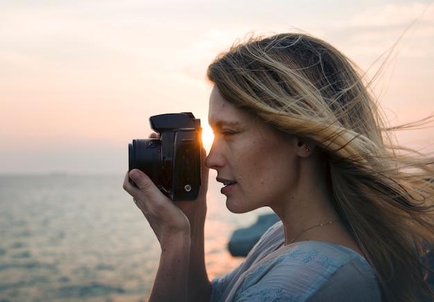 Donna con fotocamera riprese sulla spiaggia Foto Gratuite