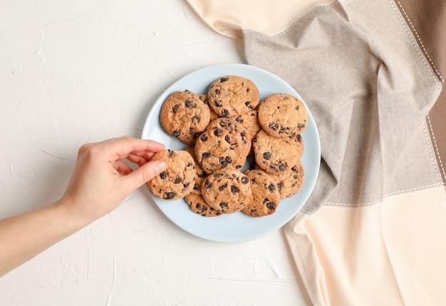 Donna con i biscotti di pepita di cioccolato saporiti su fondo grigio, vista superiore. Foto Premium