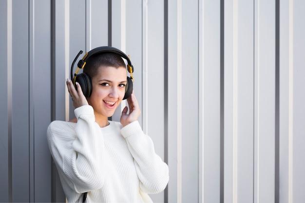 Donna con i capelli corti che ascolta la musica in cuffia e guardando la fotocamera Foto Gratuite