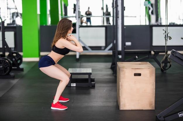Donna con i capelli lunghi sta lavorando con simulatore di sport box passo nella palestra fitness Foto Gratuite
