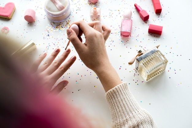 Donna con i capelli rosa facendo smalto   Foto Premium